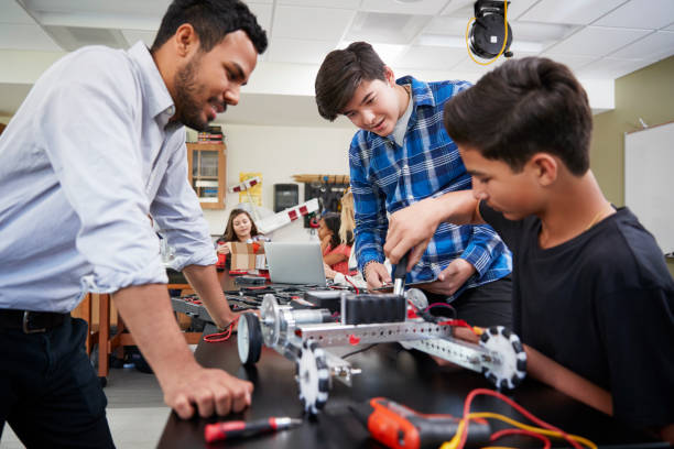 Teacher With Male Pupils Building Robotic Vehicle In Science Lesson stock photo