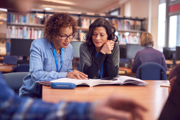 Teacher With Mature Female Adult Student Sitting At Table Working In College Library stock photo
