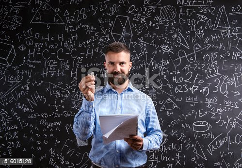 istock Teacher with notebook against big blackboard with symbols and fo 516015128