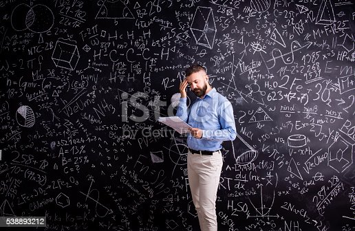 istock Teacher with notebook against big blackboard with symbols and fo 538893212