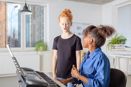 Teacher With Piano Assisting Student In Singing Stock Photo - Download Image Now
