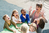 High angle view of a preschool teacher with a multi-ethnic group of children, 4 to 5 years, laughing and having fun.  They are sitting at a green table outdoors, mouths open, laughing and shouting.