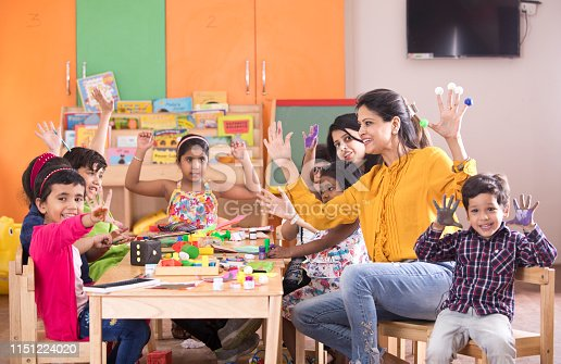 Teacher with preschool students having fun while finger painting at class
