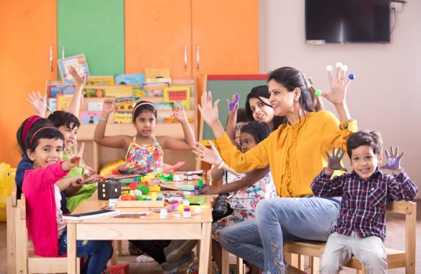 lehrer mit vorschulern fingermalerei im unterricht - kindergarten workshop stock-fotos und bilder