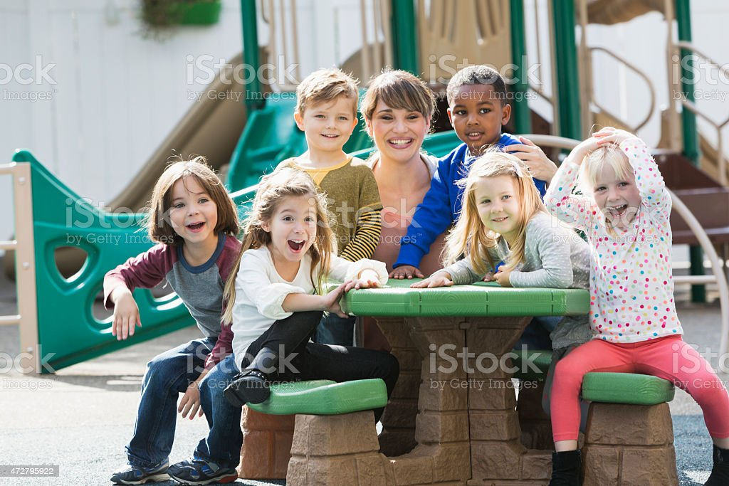Teacher with preschoolers on playground laughing stock photo