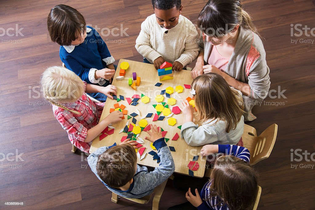 Teacher with preschoolers playing with colorful shapes stock photo