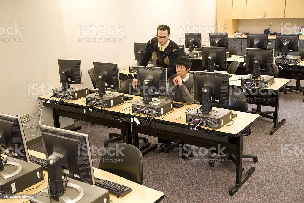 Professor com Menino de escola (16-17) a trabalhar no computador sala foto de stock royalty-free