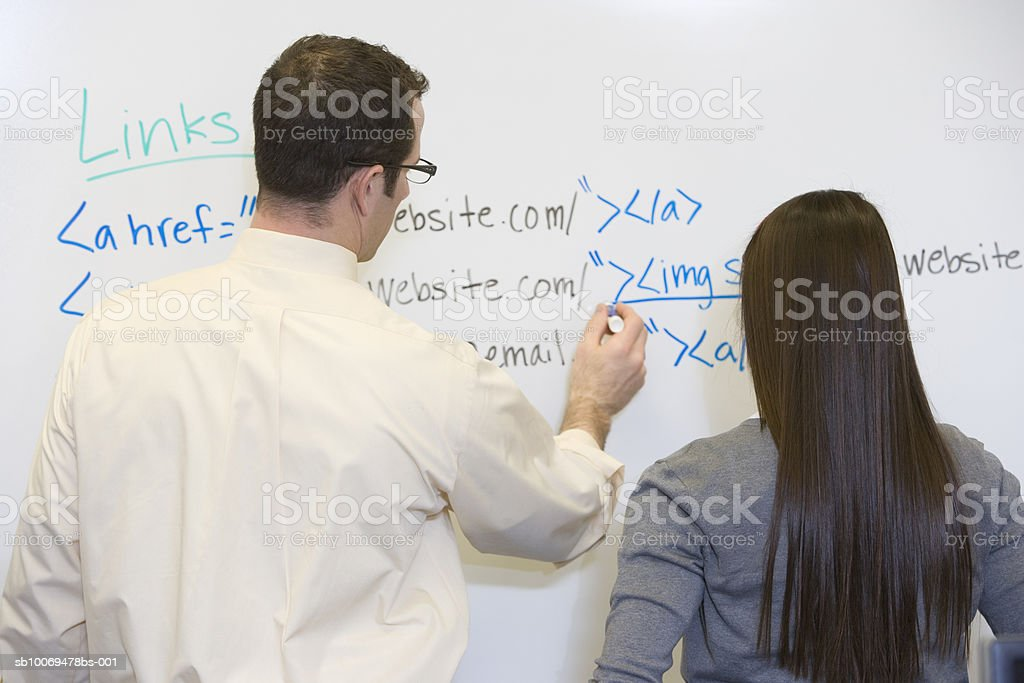 Teacher with school girl (16-17) writing on board in classroom, rear view royalty-free stock photo