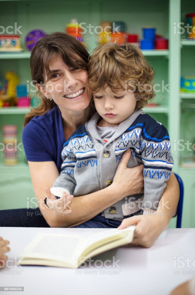 Portrait of smiling mature female teacher with a little boy sitting...