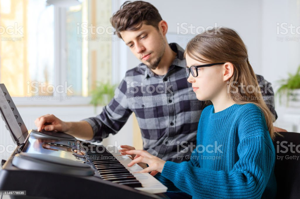 Teacher with student playing piano in class Pianist looking at female student while playing piano. Pre-adolescent girl is learning music in conservatory. They are in training class. 10-11 Years Stock Photo