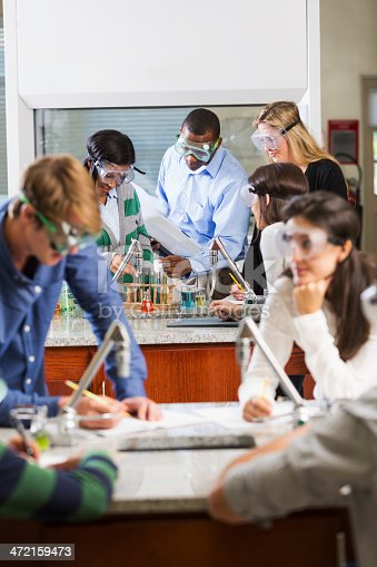 istock Teacher with students in chemistry class 472159473