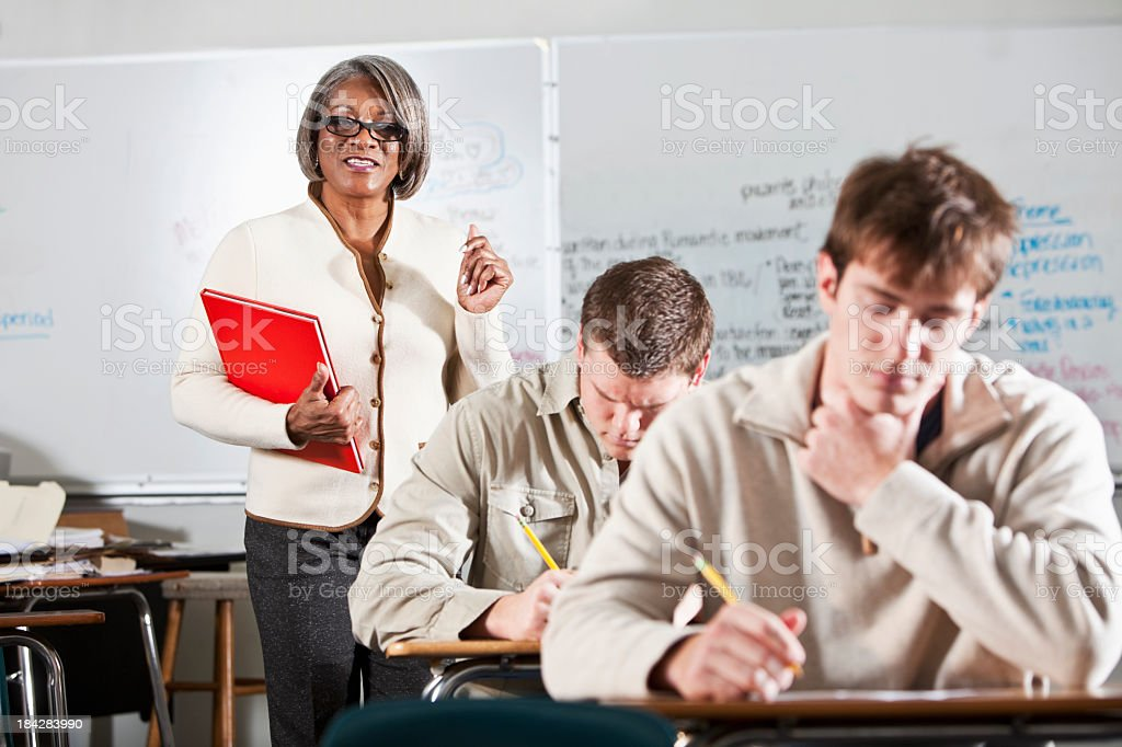 Teacher with students taking test royalty-free stock photo