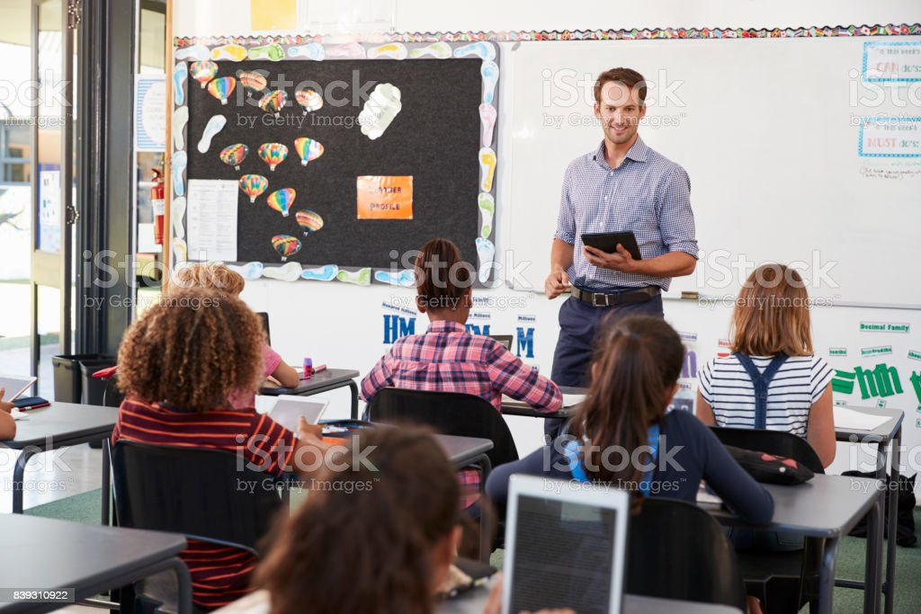 Teacher with tablet in front of elementary school class stock photo