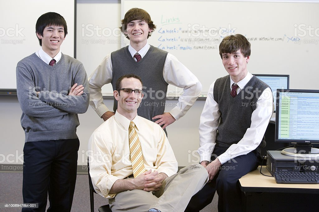 Teacher with three school boys (16-18) in computer room, portrait royalty-free stock photo