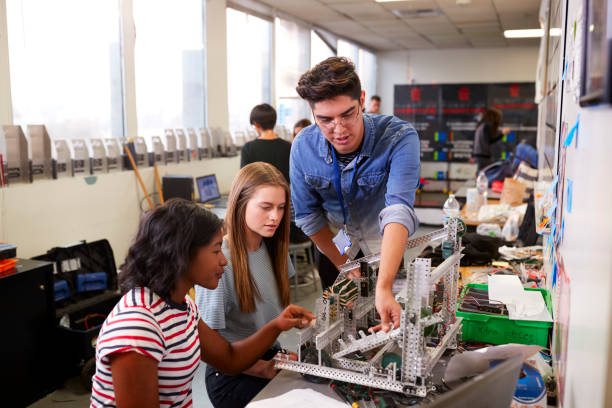 Teacher With Two Female College Students Building Machine In Science Robotics Or Engineering Class Teacher With Two Female College Students Building Machine In Science Robotics Or Engineering Class high school teacher stock pictures, royalty-free photos & images