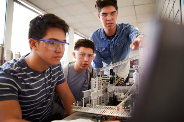 profesora con dos estudiantes universitarios masculinos construyendo una máquina en robótica científica o clase de ingeniería - robótica fotografías e imágenes de stock