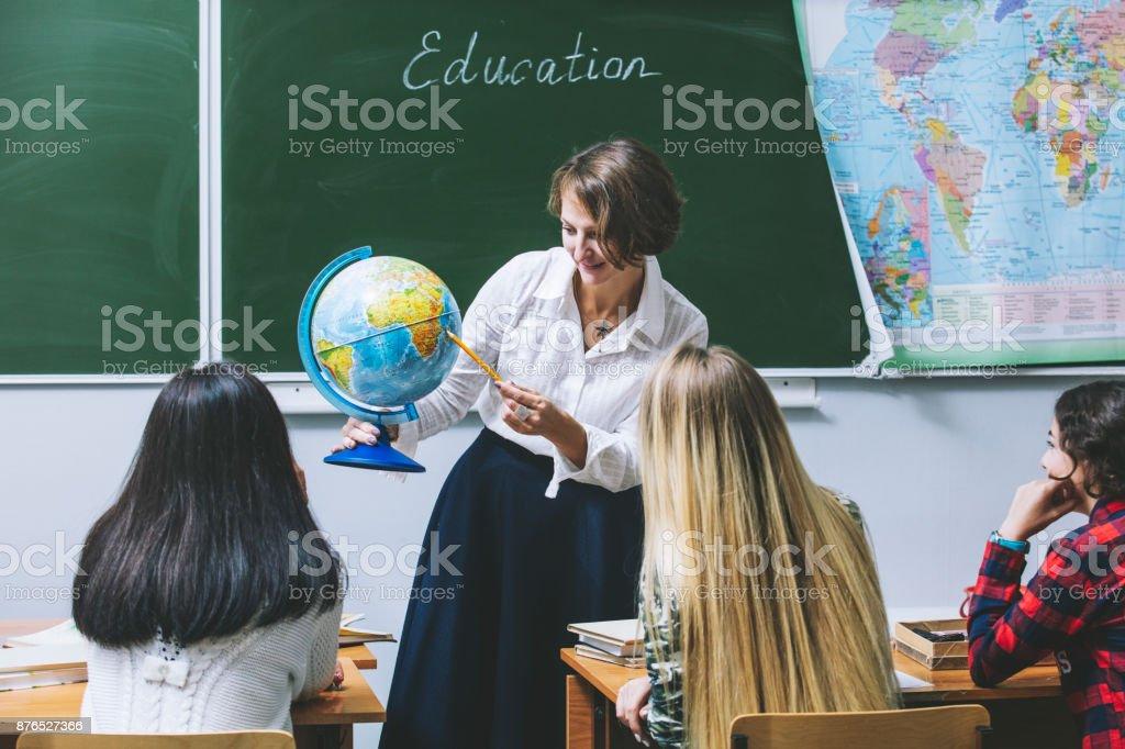 Maestro mujer felizes jóvenes conduce una lección en clase - foto de stock