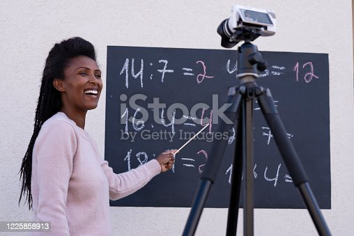 Happy teacher woman teaching remotely online in live, broadcasting math class during the Coronavirus, using mirrorless video camera and tripod, standing against the blackboard, pointing to the chalk written numbers.