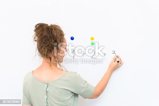 istock teacher woman teaches how to count on whiteboard in the classroom 824628560