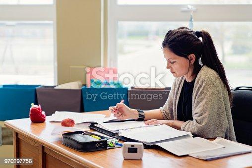 840623374 istock photo Teacher working at her desk in empty classroom. 970297756