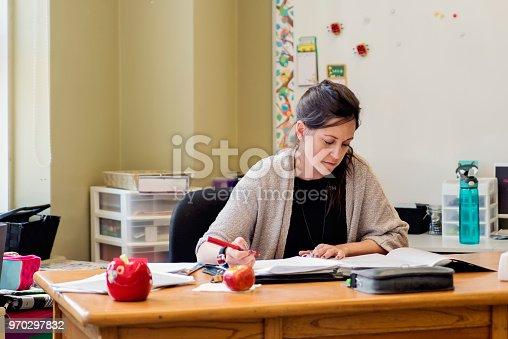 840623374 istock photo Teacher working at her desk in empty classroom. 970297832