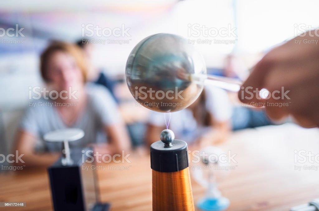 Maestros trabajando en proyecto de bobina de tesla en clase - foto de stock