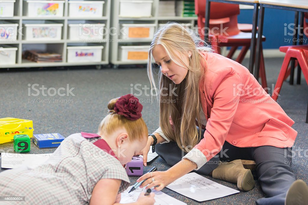 Teacher Working With a School Girl Sitting on the Floor stock photo