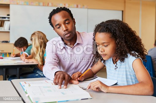 istock Teacher working with elementary school girl at her desk 1045322212