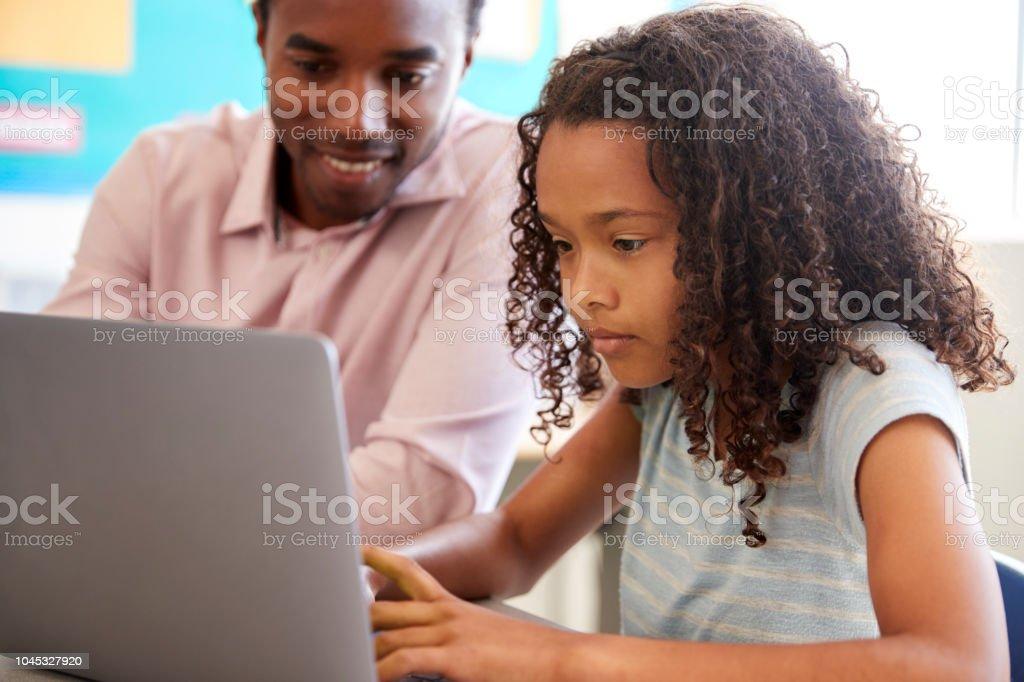 Lehrer arbeiten mit Grundschule Mädchen am laptop – Foto
