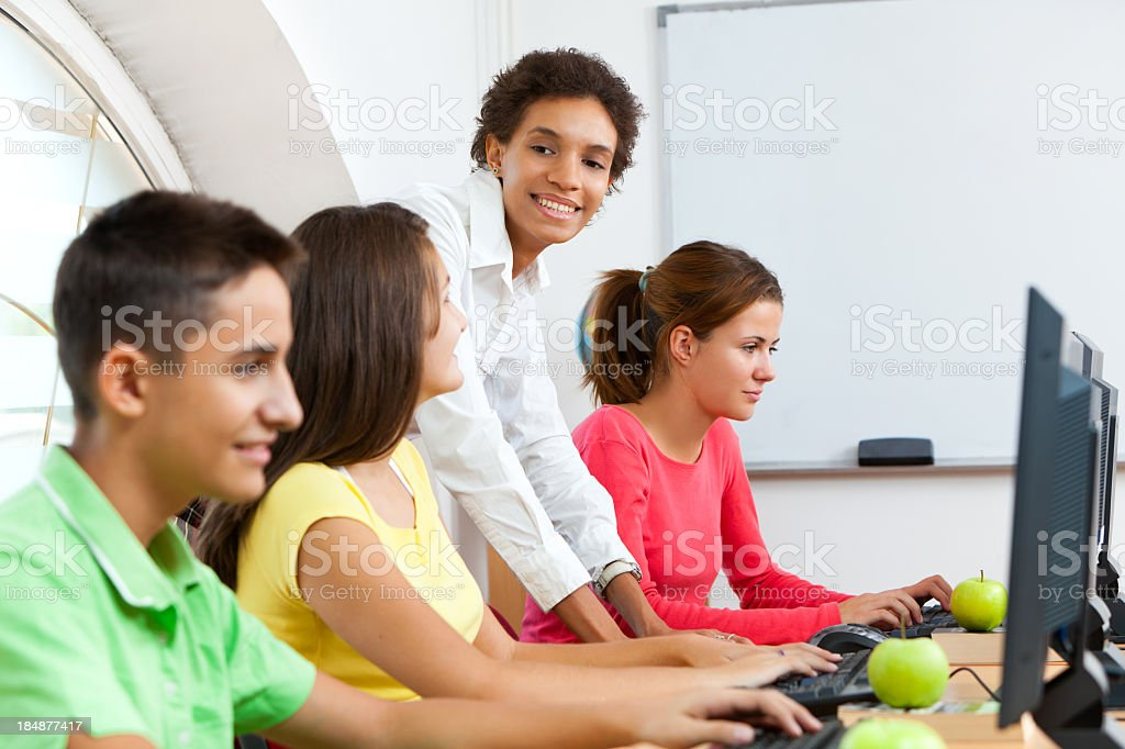 Teacher working with students on computers in the classroom royalty-free stock photo