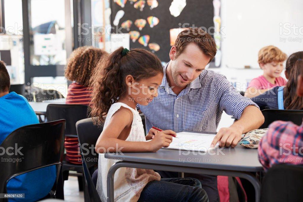 Maestro trabaja con colegiala joven en su escritorio en clase - foto de stock