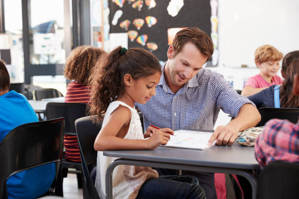 Teacher working with young schoolgirl at her desk in class stock photo