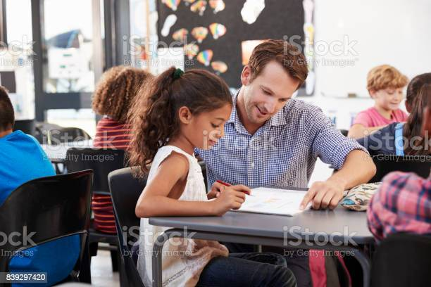 Teacher Working With Young Schoolgirl At Her Desk In Class Stock Photo - Download Image Now