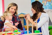 Caucasian mother and daughter work with preschool teacher. They are sitting at a table in the classroom working with educational toys.
