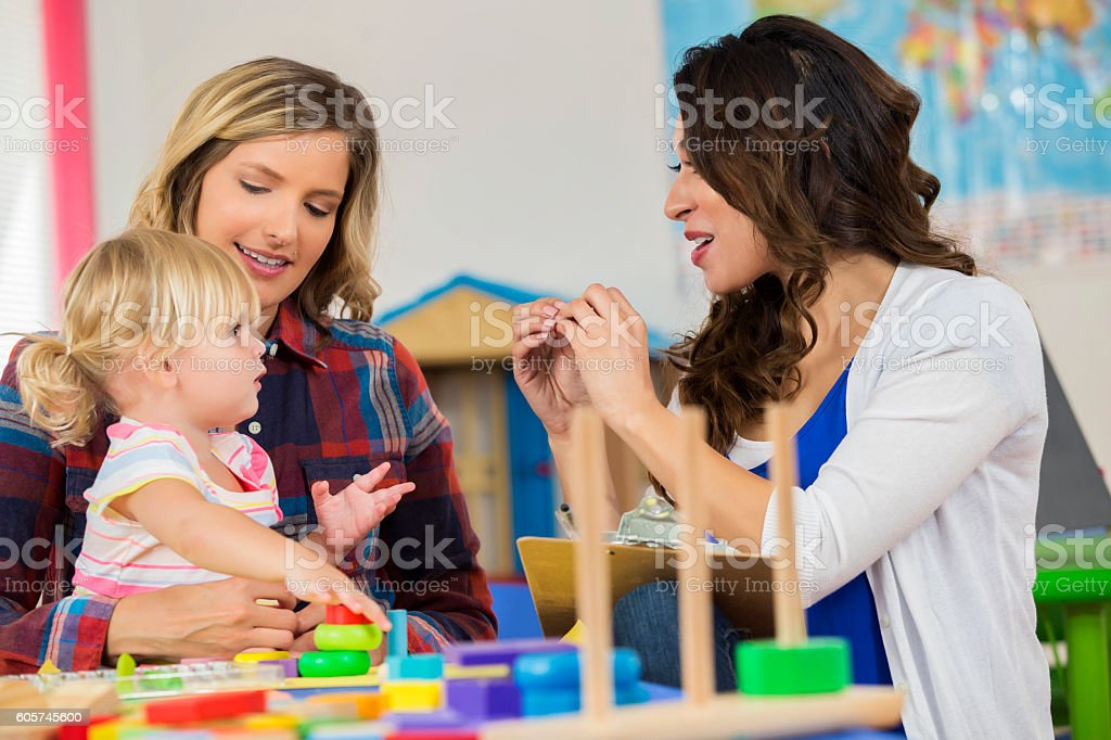 Teacher works with preschooler sitting on mother's lap stock photo