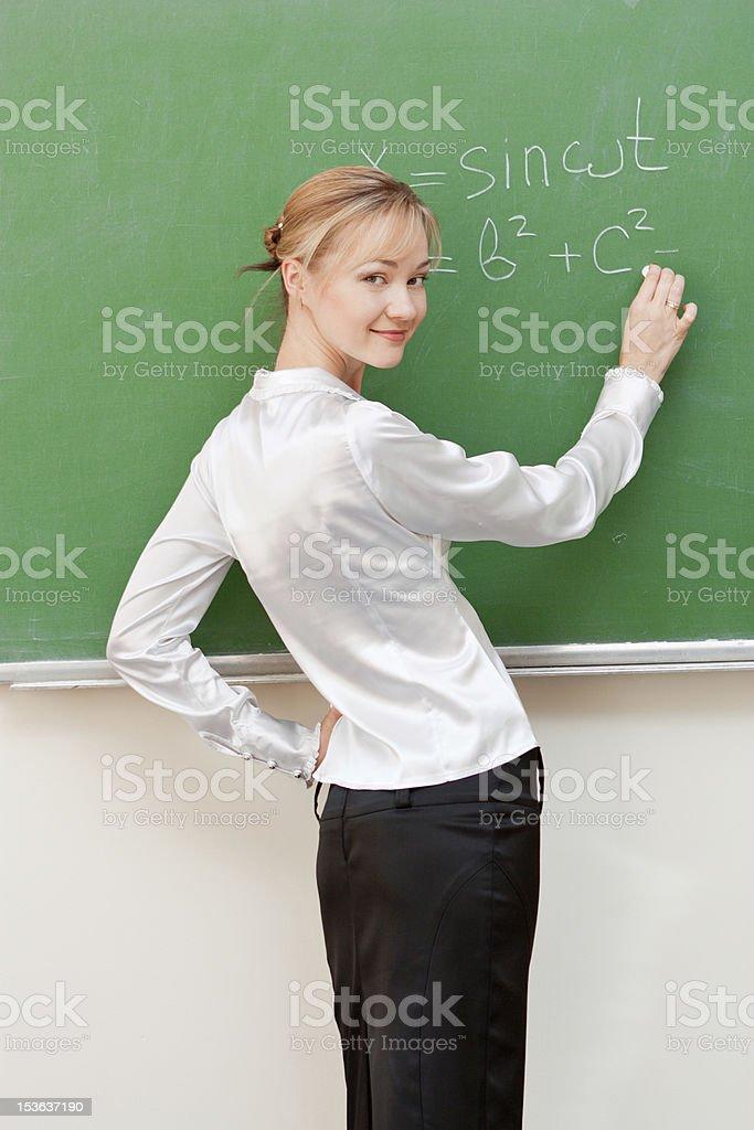 teacher writes on blackboard royalty-free stock photo