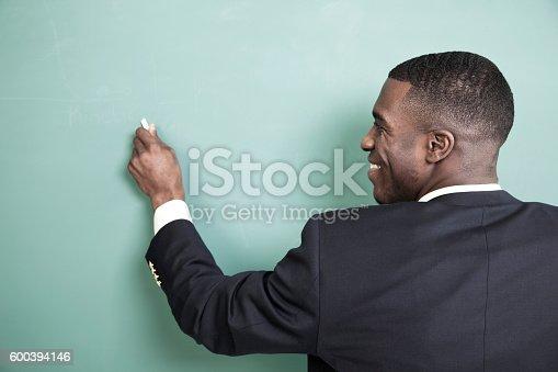 istock Teacher writes on chalkboard in high school classroom. 600394146