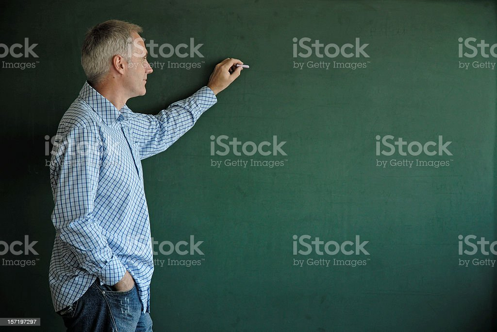teacher writing at blackboard royalty-free stock photo