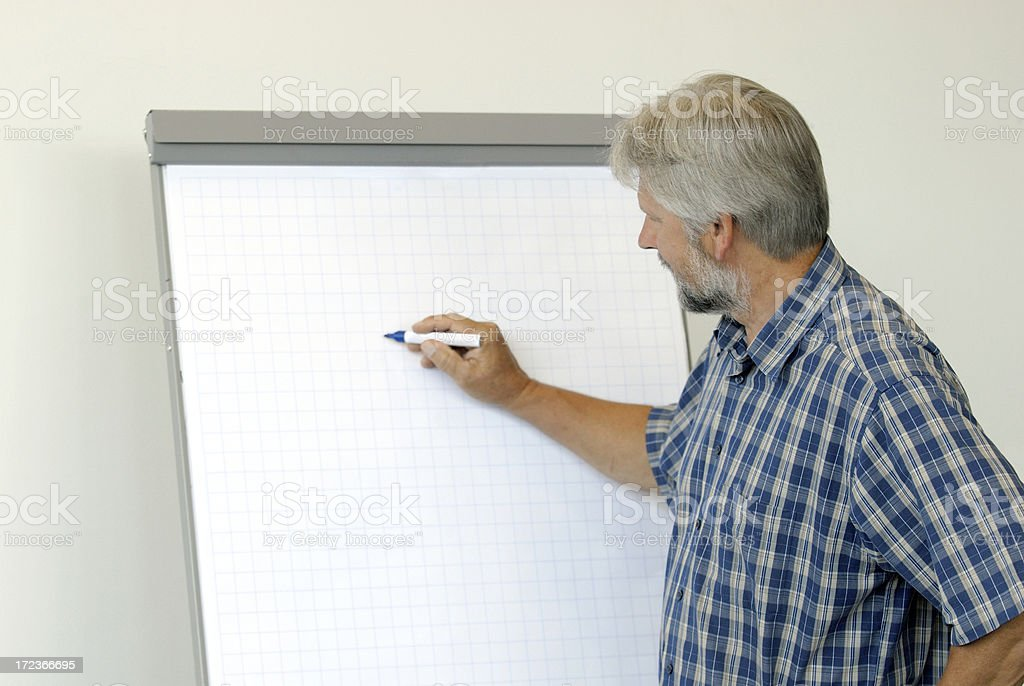 A teacher writing on a whiteboard royalty-free stock photo