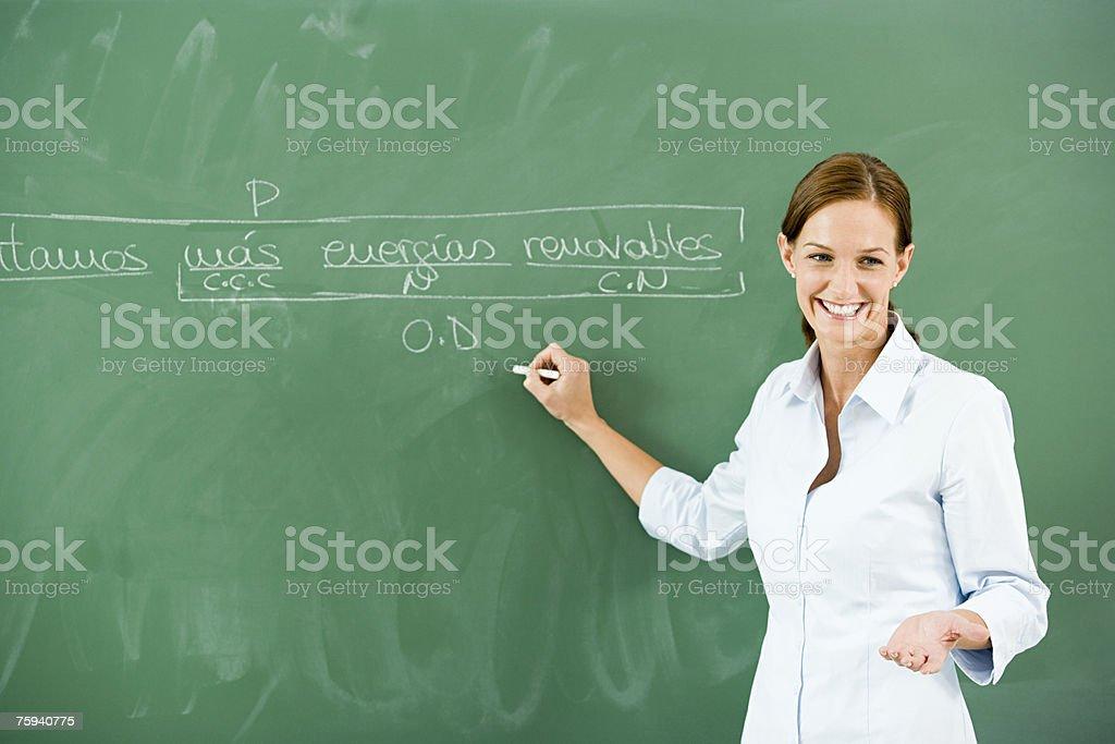 Teacher writing on blackboard stock photo