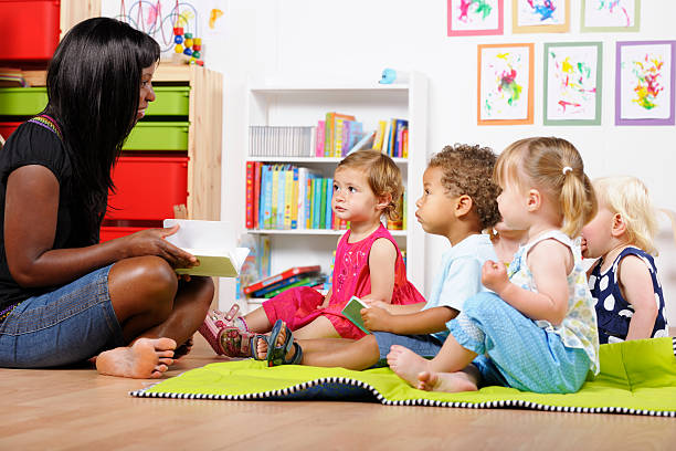 Teacher/Carer/ Childminder Reading To A Group Of Toddlers At Nursery stock photo