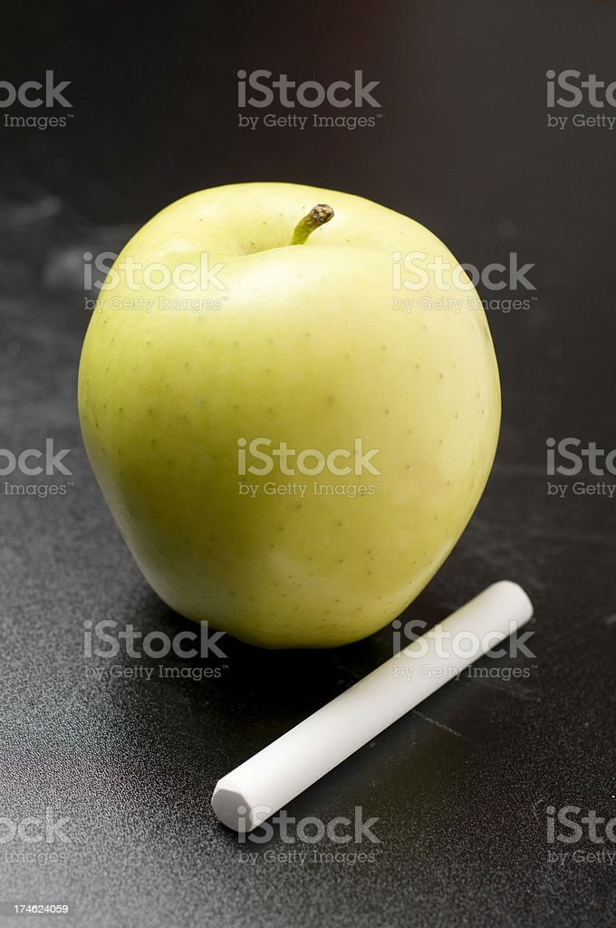 Apple and chalk on a blackboard.