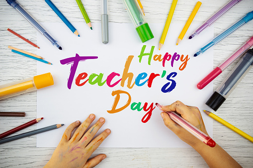 Little child is drawing on paper about teachers day. Happy Teachers Day