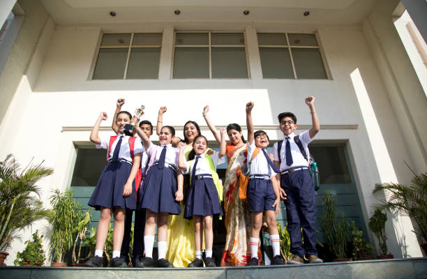 Lehrer mit Schülern feiern Erfolg – Foto