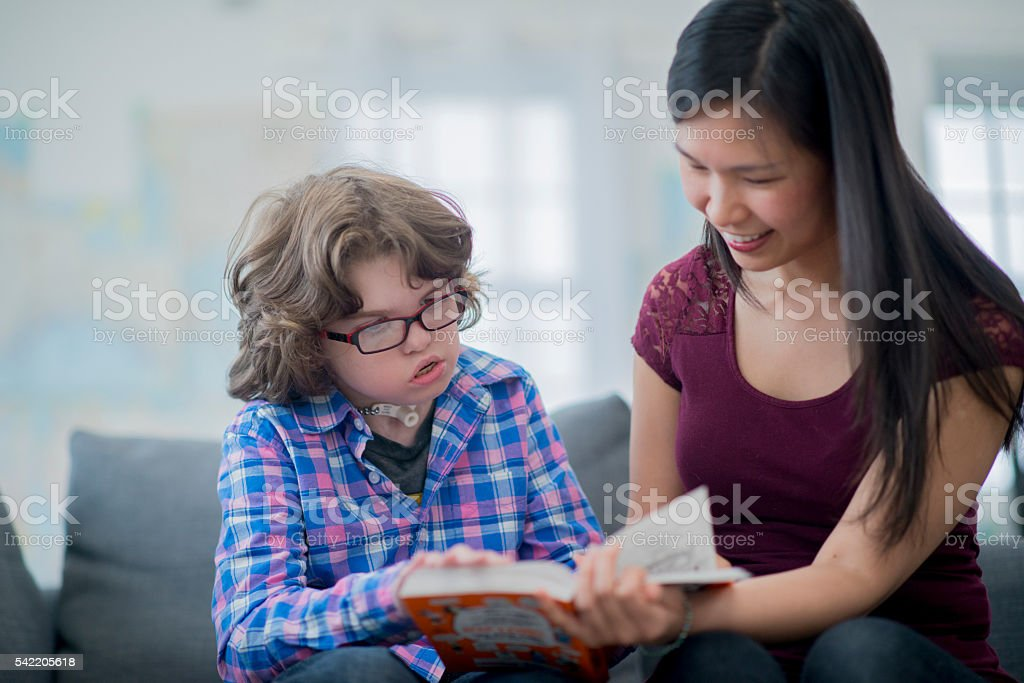 An elementary age boy is sitting with his homeschooling instructor...