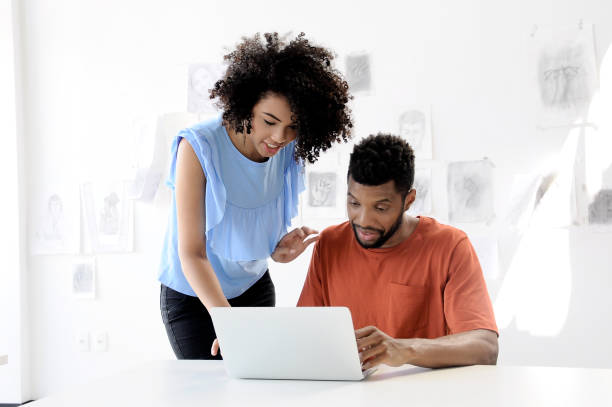 Teaching and learning laptop afro couple stock photo