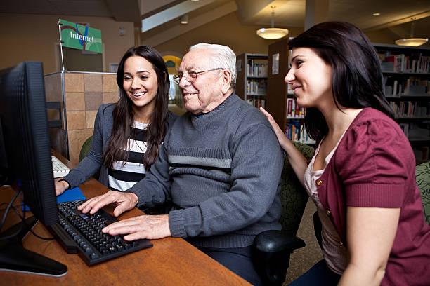 Teaching grandpa how to surf the net stock photo
