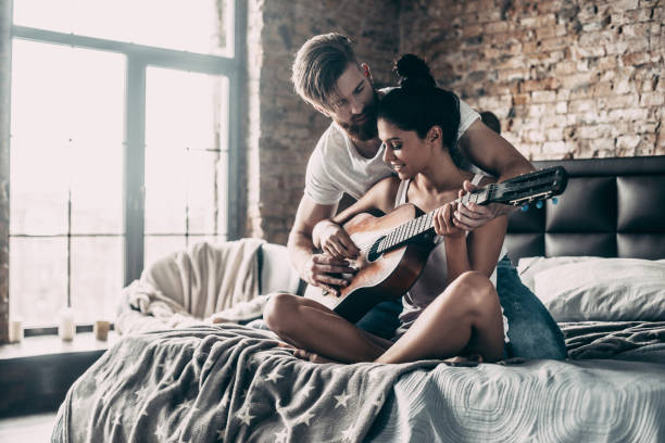 Teaching her to play guitar. stock photo