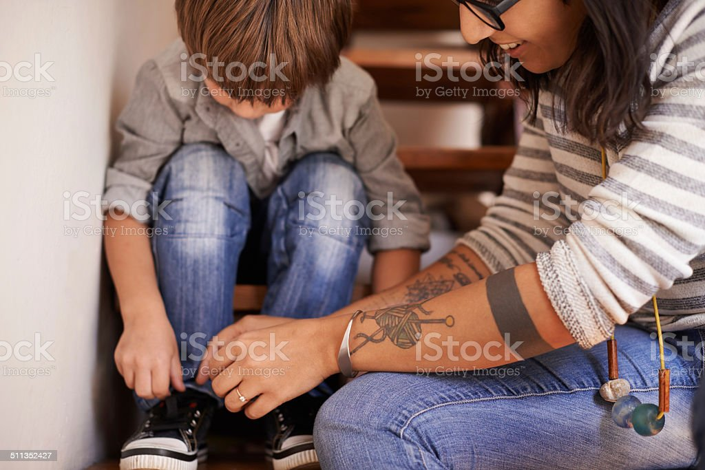 Teaching him to tie his shoes stock photo