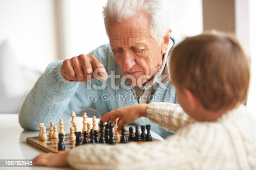 A grandfather teaching his grandson how to play chess